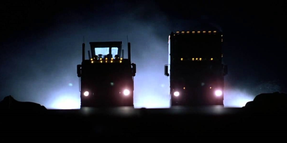 Headlights of two oncoming semi trucks